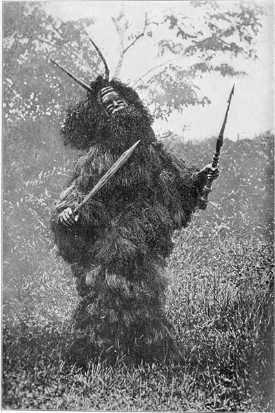 rontispiece from book. Fetich Magician with horns, wooden mask, spear, and sword ; dress of leaves of palm and plantain. ource=Fetishism in West Africa: Forty Years' Observations of Native Customs and Superstitions Date=1904