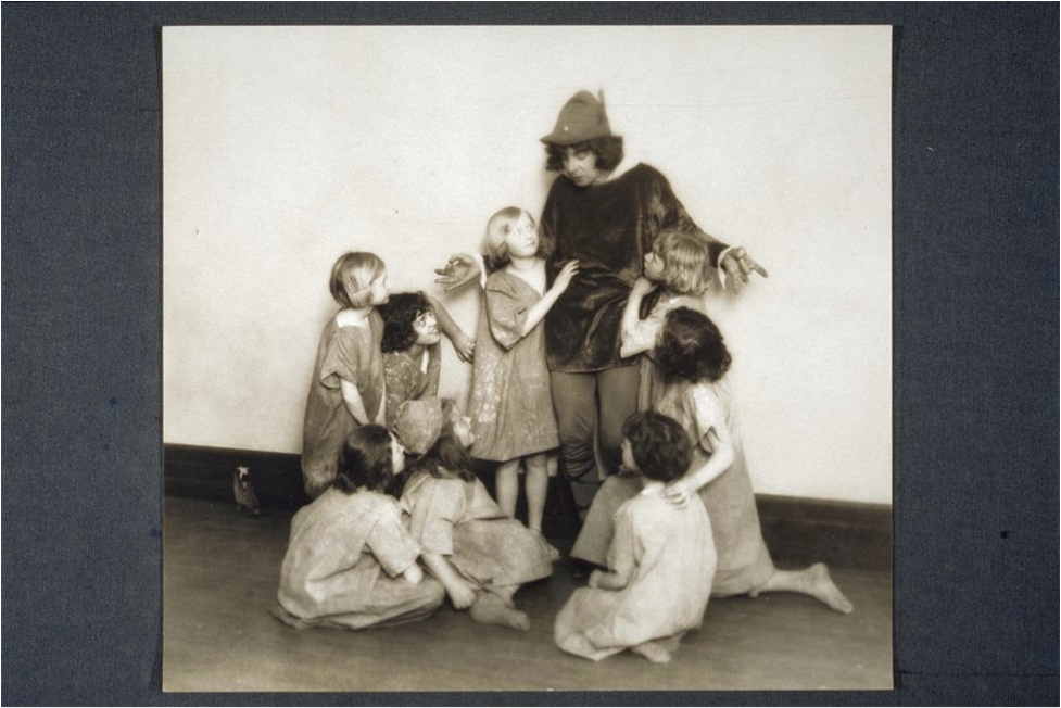 Creator: Beals, Jessie Tarbox (New York, N.Y.); Title: Actor shrugging his shoulders as he looks down at eight girls both seated and standing around him. Actor holds both hands so that his thumbs and middle fingers touch.; Work Type: photographs; g